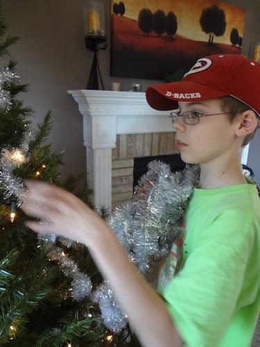 joel putting garland on tree