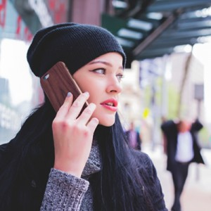 woman with dark hair wearing a beanie and talking on a phone