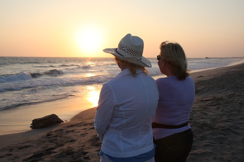 two women at beach at sunset