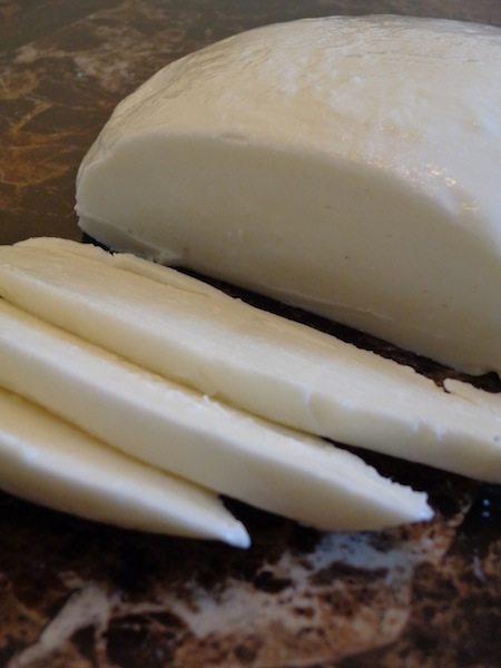 Homemade Mozzarella Cheese with three slices cut