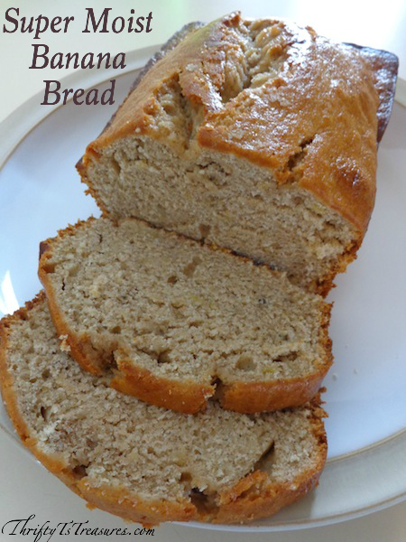 Loaf of banana bread on a plate with two slices cut