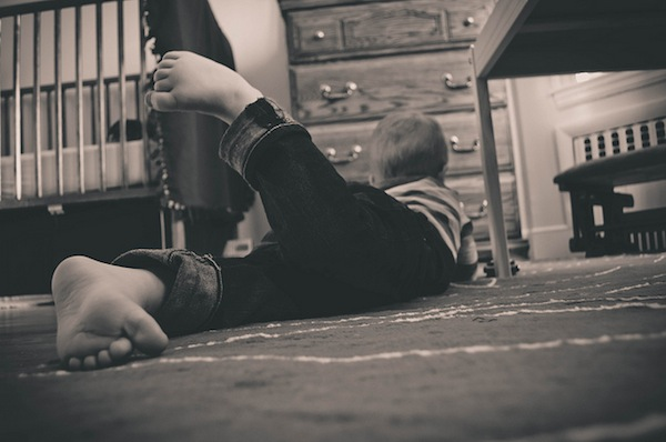 little boy laying on the floor in his room playing