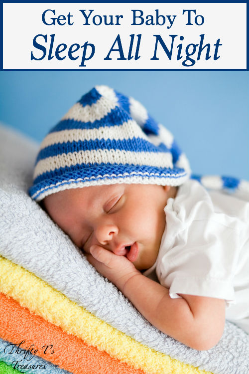 infant sleeping on a stack of colorful towels