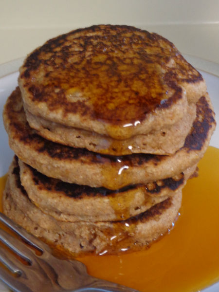 stack of cinnamon applesauce pancakes being drizzled with maple syrup