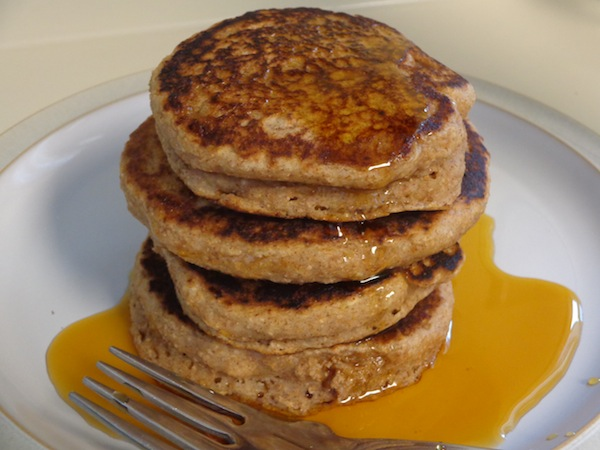 stack of four cinnamon applesauce pancakes covered in maple syrup