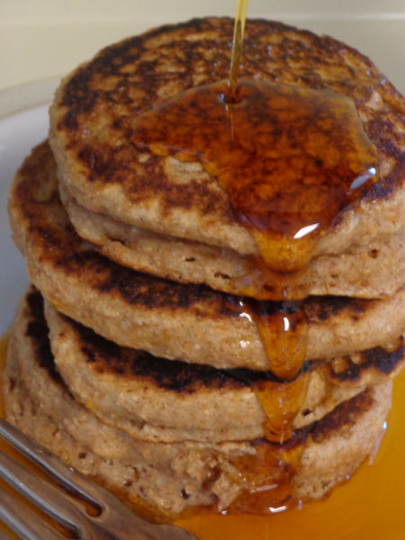 stack of four cinnamon applesauce pancakes with maple syrup being pour over them
