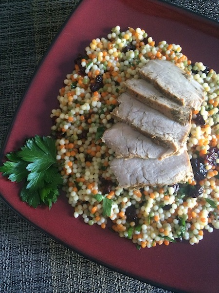 slices of pork tenderloin on a bed of multi-color cranberry lemon couscous