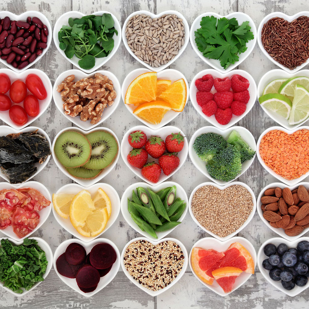 heart shaped bowls filled with fruits, vegetables and grains