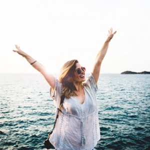 woman standing in front of ocean with hands in the air
