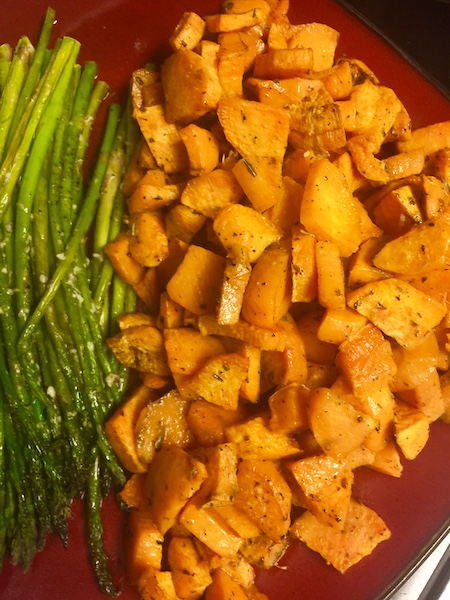 maroon colored plate topped with oven roasted sweet potatoes and garnished with roasted asparagus