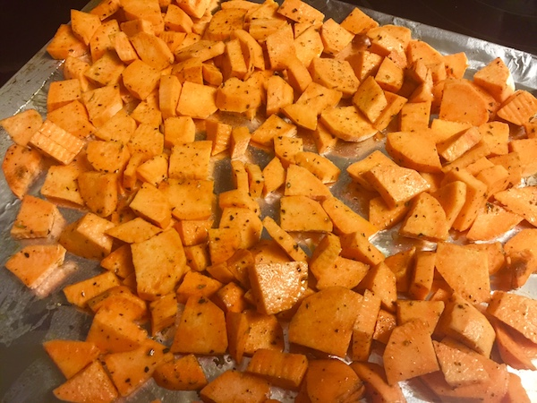 diced and seasoned sweet potatoes on top of a foil wrapped cookie sheet
