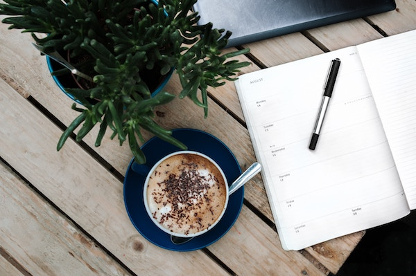 cup of coffee, laptop, open planner and green plant on top of a desk