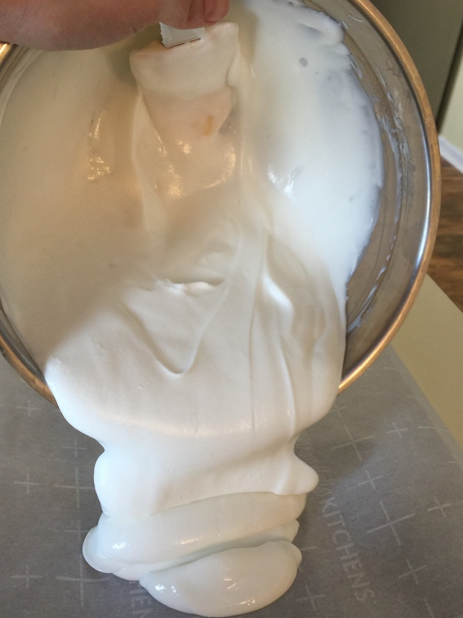 yogurt being poured into a pan lined with parchment paper