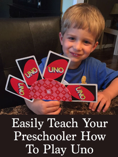 little boy holding uno cards