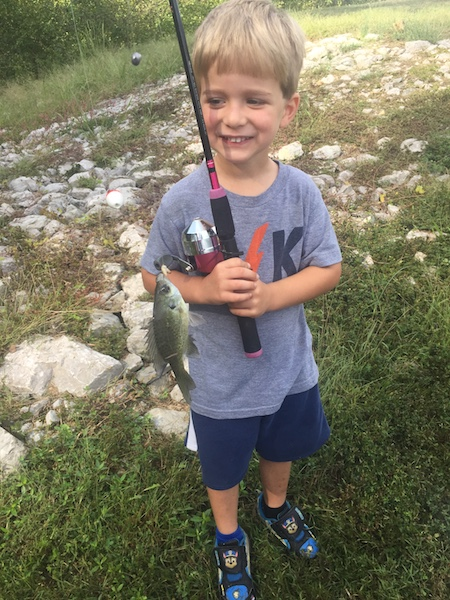 Dalton holding fishing rod and a fish he caught