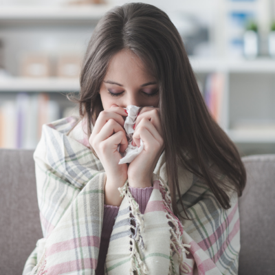 woman wrapped in a blanket and blowing her nose