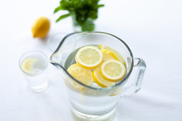 pitcher of water with lemons on top