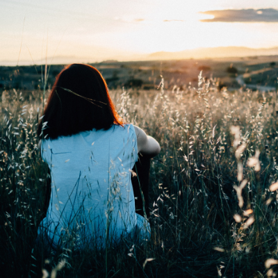 woman sitting in grassy hill watching sunset