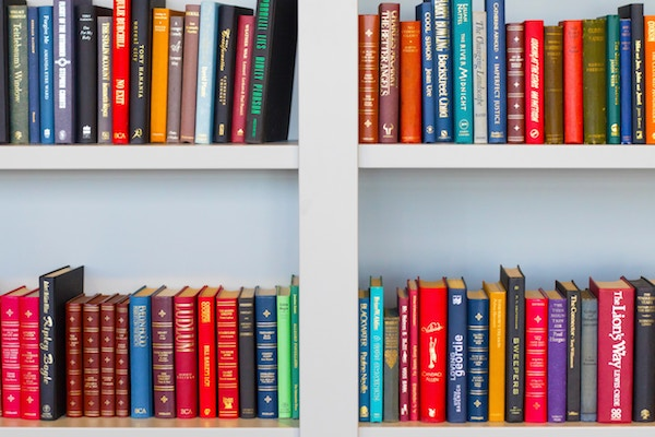 colorful books on a white bookshelf 600x400