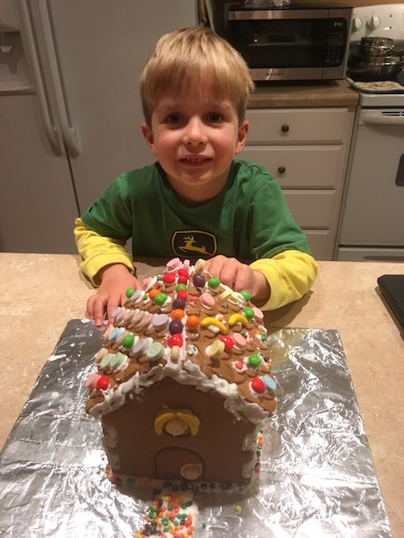 little boy with a gingerbread house