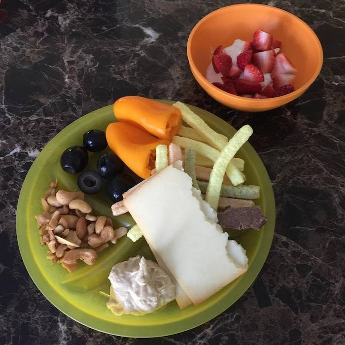 plate of food including cheese, hummus, veggie straws