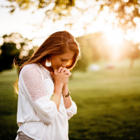 woman praying in grassy area