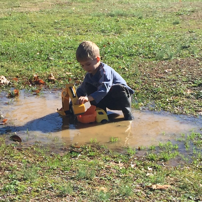 little boy playing in mud puddle