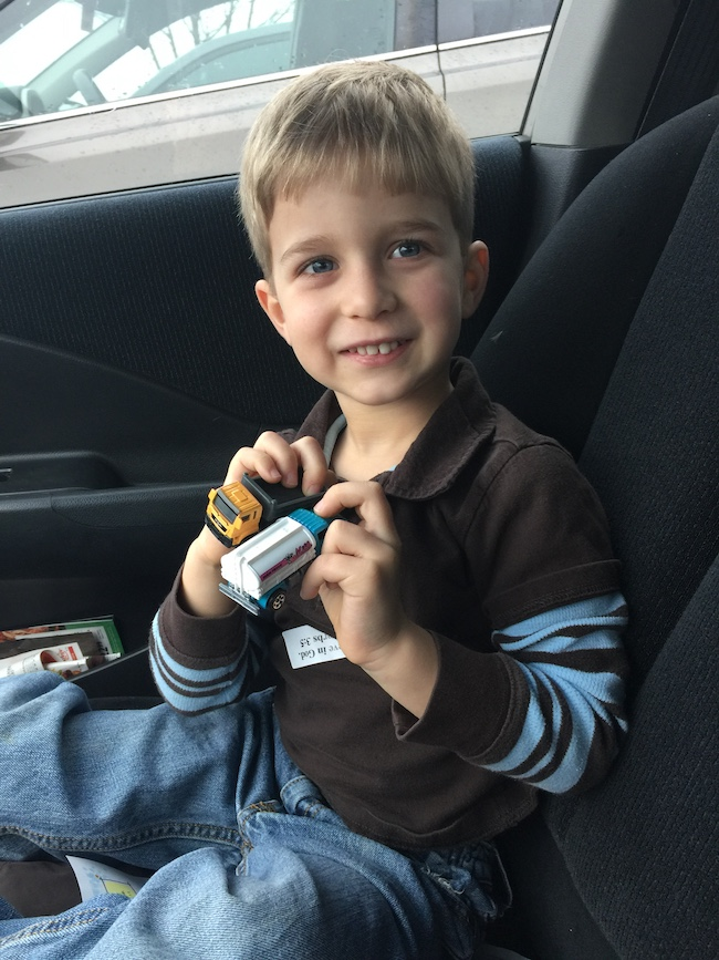 little boy holding two matchbox cars
