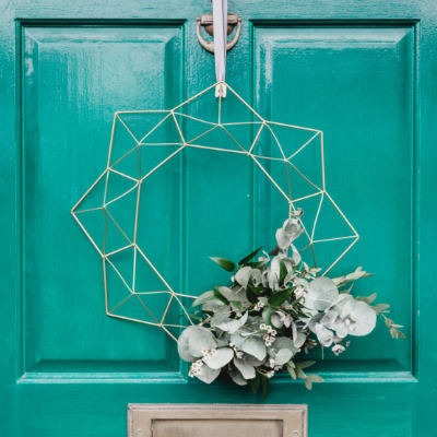 teal front door with silver wired and white flowered wreath
