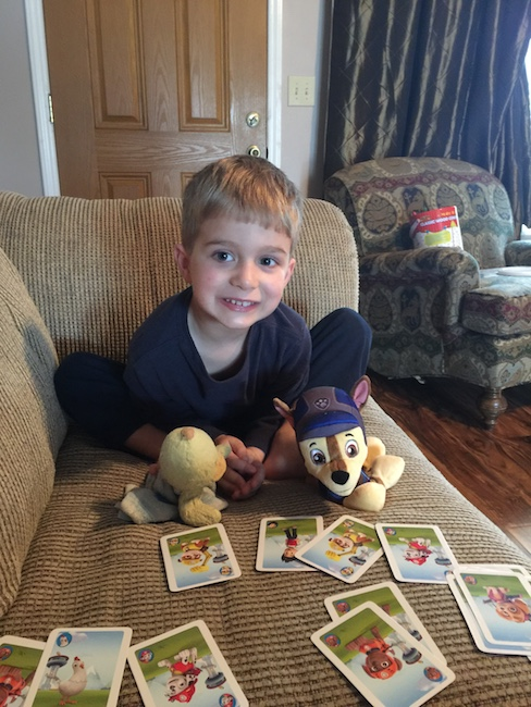 little boy with stuffed animals playing cards