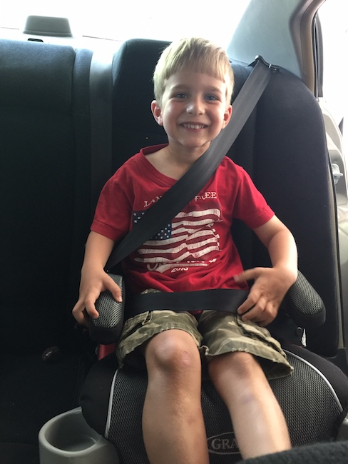 little boy in booster seat