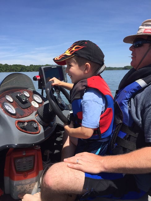 little boy sitting on his dad's lap driving a boat