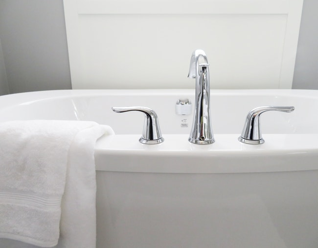 white bathtub with towel hanging over the side