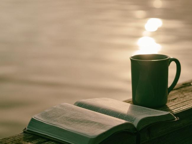 bible and coffee mug on dock