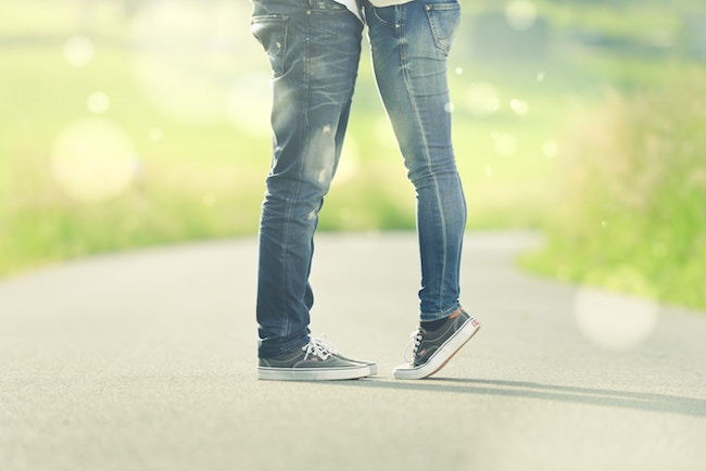 couple facing each other with girl standing on tip toes