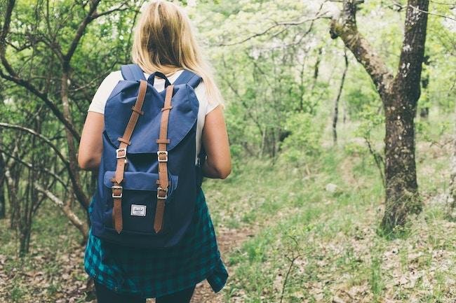 female hiking through woods