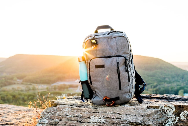 grey and black hiking backpack and cyan tumbler on grey rock during sunset