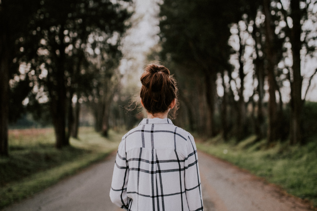 woman walking down a road with trees on the both sides