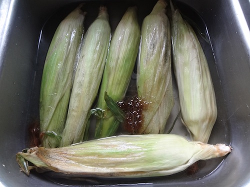 corn on the cob soaking in water
