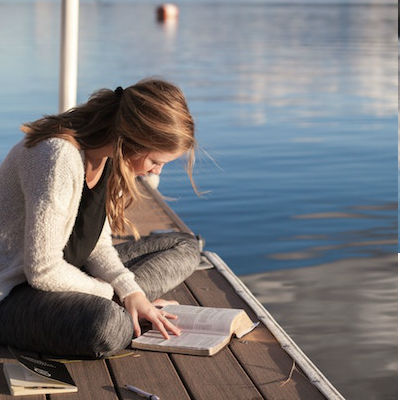 woman sitting on dock reading a book