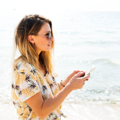 woman at ocean holding a cell phone