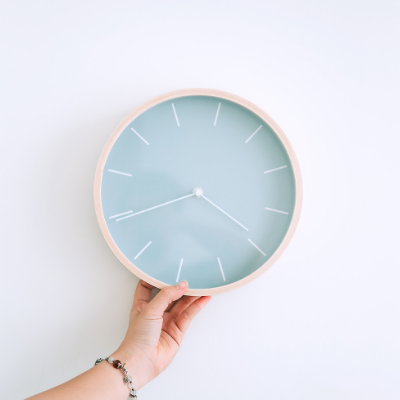 hand holding clock with blue face