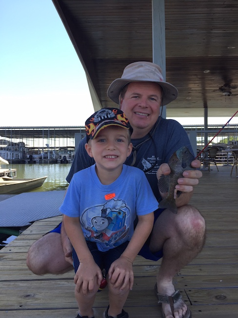 father and son holding a fish