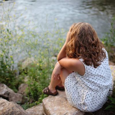 woman sitting alone by the lake