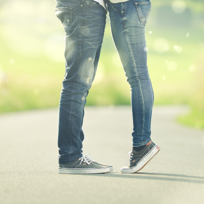 couple facing each other with girl standing on tip toe
