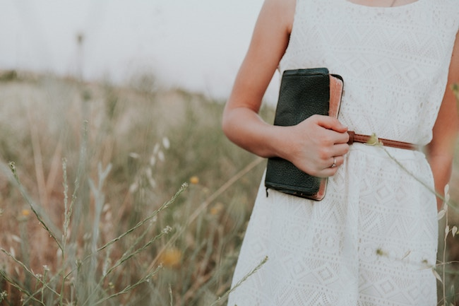 woman standing in field holding bible