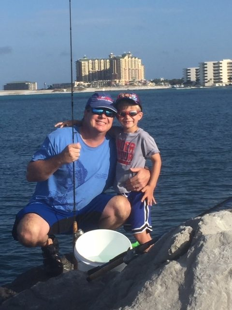 father and son fishing on jetties in Destin