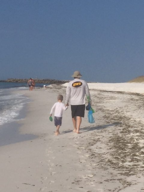 father and son walking down beach