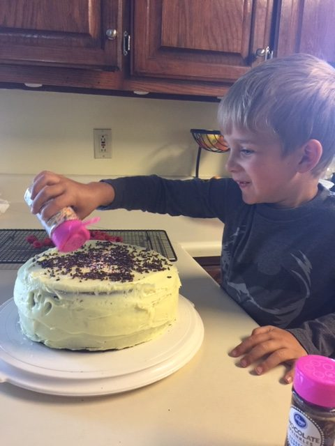 little boy decorating birthday cake