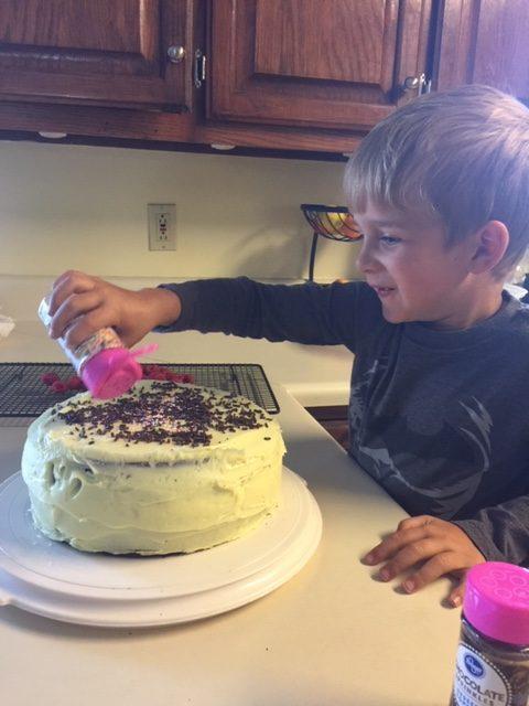 little boy decorating birthday cake